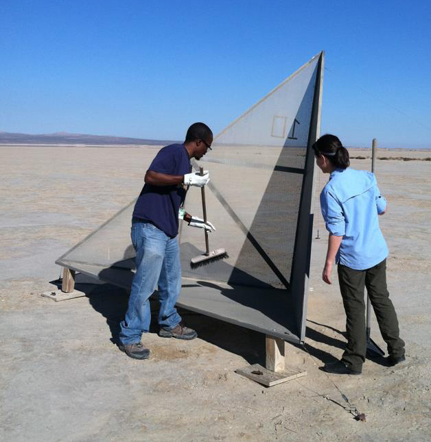 two people standing next to a corner reflector